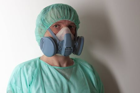Male nurse, with twin filter half face respirator mask , cap, gown,  with personal protective equipment to protect against the virus covid-19 in ICU in hospital.