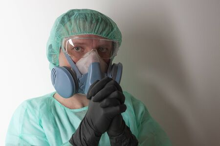 Male nurse, with twin filter half face respirator mask , protective eyglasses,  cap, gown,  with  personal protective equipment to protect against the virus covid-19 in ICU in hospital. Stock Photo