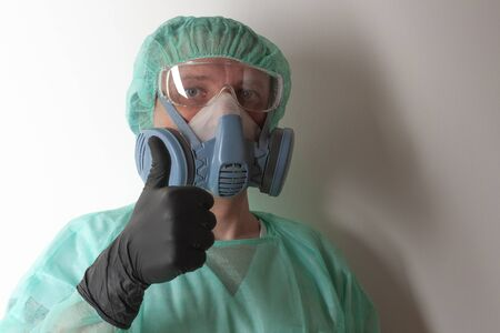 Male nurse, with twin filter half face respirator mask , protective eyeglasses,  cap, gown,  with  personal protective equipment to protect against the virus covid-19 in ICU in hospital.