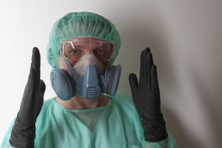Male nurse, with twin filter half face respirator mask , protective eyeglasses,  cap, gawn,  with  personal protective equipment to protect against the virus covid-19 in ICU in hospital. Stock Photo
