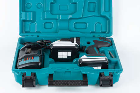 Cordless hammer screwdriver drill, battery charger and second battery in carry case on white background. Studio shoot. 写真素材