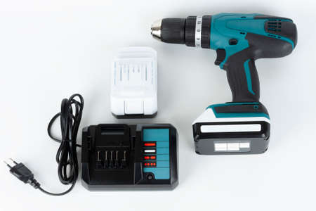 Cordless hammer screwdriver drill, battery charger and second battery on white background. Studio shoot. Archivio Fotografico