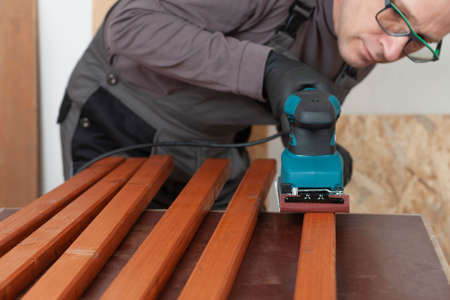 Carpenter working with electric sheet finishing sander on wooden slats for production of wooden garden bench on table in carpentry workshop Imagens