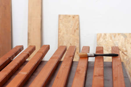 Wooden slats for production of wooden garden bench and paintbrush on table in carpentry workshop Imagens