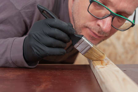 Carpenter paints wooden slat for production of wooden garden bench on table in carpentry workshop