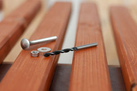 Wood drill, carriage bolt, hex nut on wooden slat for production of wooden garden bench on table in carpentry workshop