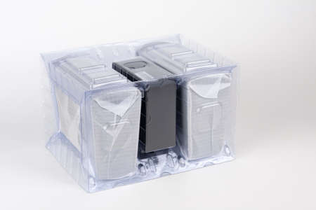 Two computer speakers in transparent plastic bag on white background. In the middle between the speakers is black box with AC adapter.