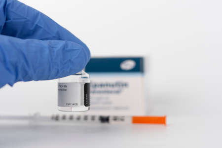 Human fingers in gloves, syringe and Covid-19 vaccine vial.