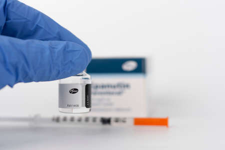 Brnenec, Czech Republic - December 12, 2020: Fingers in gloves holding vial of Epanutin. Epanutin is produced by Pfizer. Pharmaceutical corporation Pfizer also developed a vaccine on Covid-19. Editorial