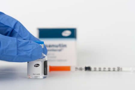 Brnenec, Czech Republic - December 12, 2020: Human fingers in gloves, vial of Epanutin. Epanutin is produced by Pfizer. Pharmaceutical corporation Pfizer also developed a vaccine on Covid-19. Editorial