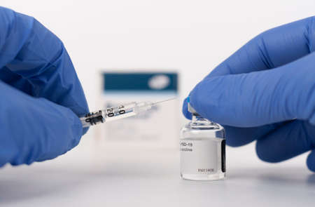 Human fingers in gloves, syringe with needle and Covid-19 vaccine vial. Stock Photo