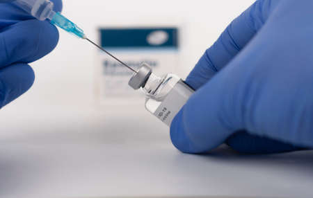 Close up human fingers in gloves, holding syringe with needle and covid-19 vaccine vial. Medical concept.