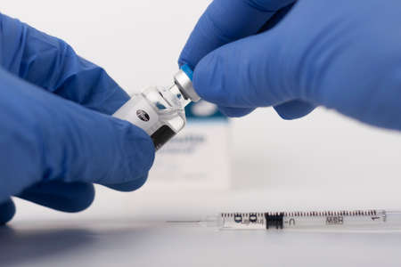 Brnenec, Czech Republic - December 12, 2020: Fingers in gloves, syringe and vial of Epanutin. Epanutin is produced by Pfizer. Pharmaceutical corporation Pfizer also developed a vaccine on Covid-19. Editorial