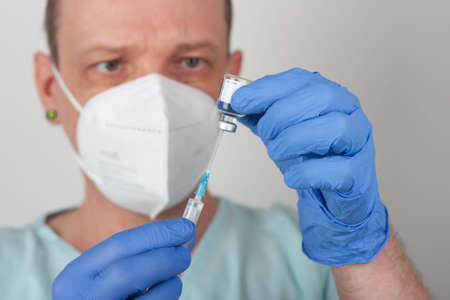 Male nurse with face mask and blue gloves, holding syringe with needle and covid-19 vaccine vial. Medical concept. Stock Photo