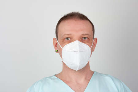 Male nurse, with respirator ffp2, with personal protective equipment to protect against the virus covid-19 in ICU in hospital. Stock Photo