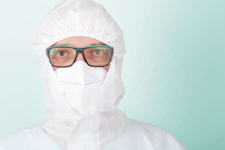 Male nurse with face mask ffp2 and protective coverall clothing. Personal protective equipment to protect against the virus covid-19 in ICU in hospital. Stock Photo