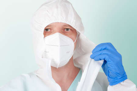 Male nurse with face mask ffp2 take off protective coverall clothing. Personal protective equipment to protect against the virus covid-19 in ICU in hospital.