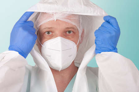 Male nurse with face mask ffp2 dress up protective coverall clothing. Personal protective equipment to protect against the virus covid-19 in ICU in hospital.