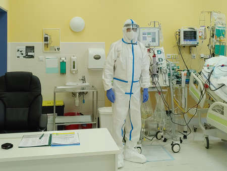 Male nurse with protective coverall clothing in intensive care unit in hospital. Dialysis machine, to which patient is connected. The patient fell ill with a new type of coronavirus covid-19. Stock fotó