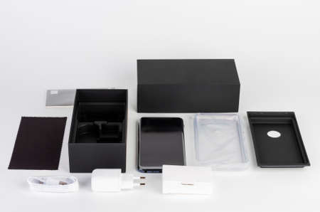 Unboxing of touchscreen smartphone, paper box, silicone cover, earphones, fast charger and clean cloth.