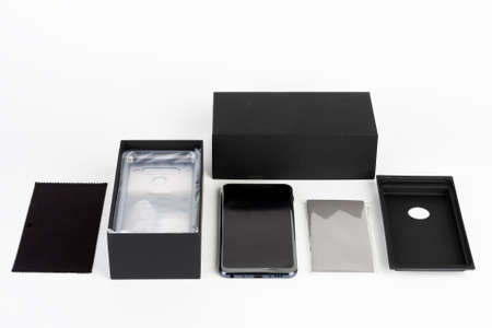 Unboxing of touchscreen smartphone, paper box and clean cloth. Studio shoot on white background. Stock Photo