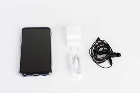 Unboxing of touchscreen smartphone, silicone cover, charger, earphones.