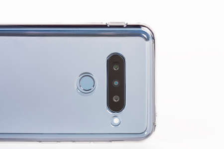 Touchscreen triple camera smartphone in silicone cover. Super Wide-Angle, standard, telephoto zoom. Fingerprint sensor. Stock Photo