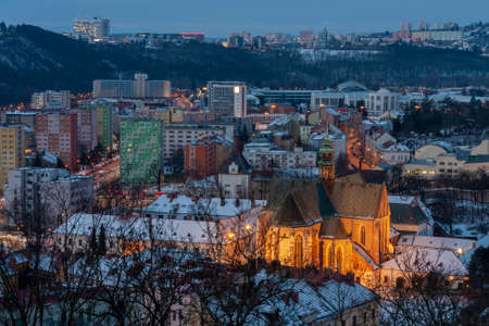 Panoramic view of the Mendel Square with The Basilica of the Assumption of Our Lady in Brno in Czech Republic. Winter sunrise time. On background under the hill Brno Exhibition center.
