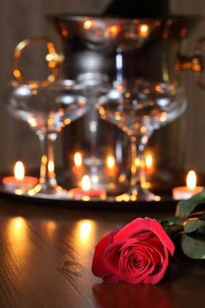 Still life with champagne, candles and red rose photo