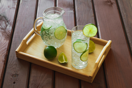 condensacion: Water drink with lime on wooden tray with ice and condensation on glass