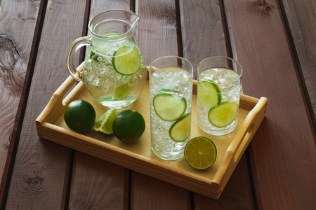 condensaci�n: Two water drinks with lime on wooden tray with ice and condensation on glass