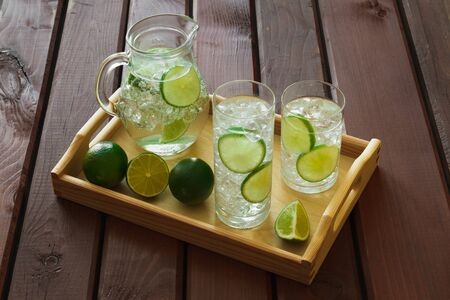 condensation: Two water drinks with lime on wooden tray with ice and condensation on glass