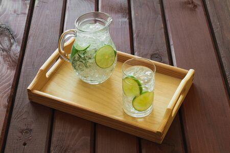 vasos de agua: Bebida del agua con la cal en la bandeja de madera con hielo y la condensación sobre el vidrio