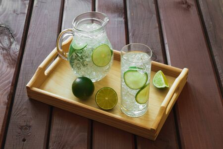 condensation: Water drink with lime on wooden tray with ice and condensation on glass