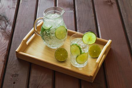 condensacion: Bebida del agua con la cal en la bandeja de madera con hielo y la condensación sobre el vidrio