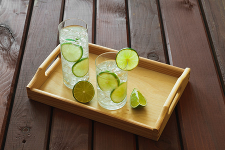 condensacion: Water drinks with lime on wooden tray with ice and condensation on glass