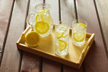 Two water drinks with lemon on wooden tray with ice and condensation on glass