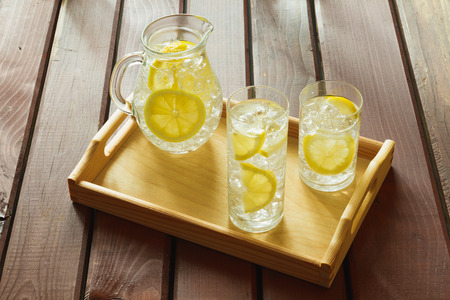 condensaci�n: Two water drinks with lemon on wooden tray with ice and condensation on glass