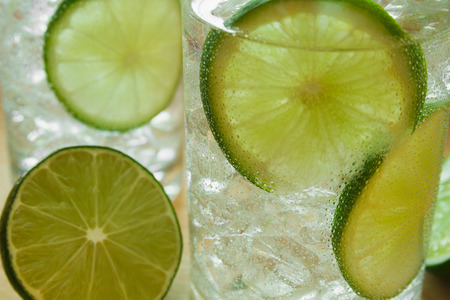 condensacion: Two water drinks with lime on wooden tray with ice and condensation on glass