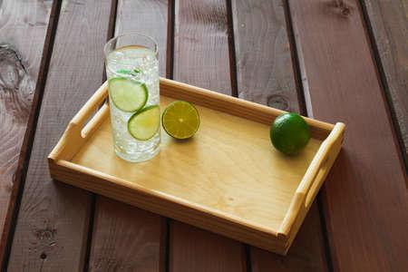 condensation: Bebida del agua con la cal en la bandeja de madera con hielo y la condensación sobre el vidrio