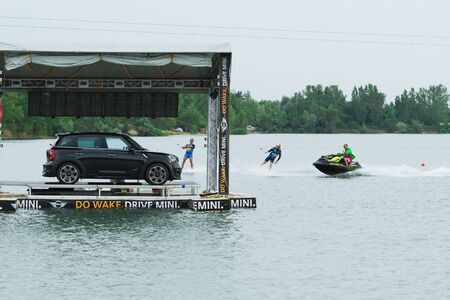 mini car: BRATISLAVA, SLOVAKIA - JUNE 27, 2015: wakeboarders Sam de Haan and Dominik Guhrs ride on one hook behing Mini car while WakeLake Golden Trophy, Contest of Wake-boarding and Wake-skating