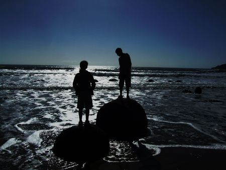 new zealand beach: Two boys standing on a rock in the beach somewhere in New Zealand Stock Photo