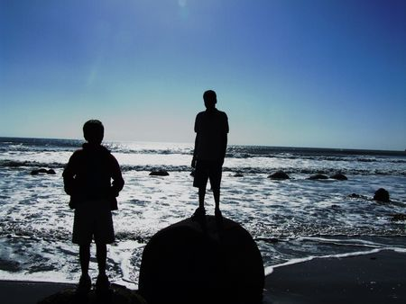 Two boys standing on a rock in the beach somewhere in New Zealand photo