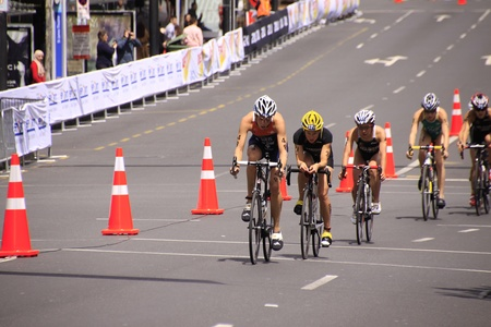AUCKLAND, New Zealand- Oct. 20,2012: Women participants in the ITU World Triathlon Grand Finale Series cycle the main street of downtown Auckland.