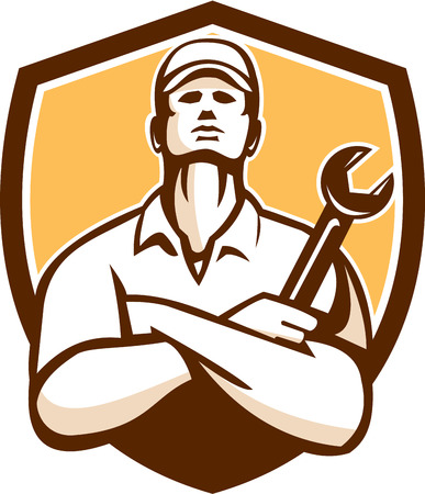 Illustration of a mechanic worker wearing hat arms crossed holding wrench looking up set inside shield crest on isolated background done in retro style.