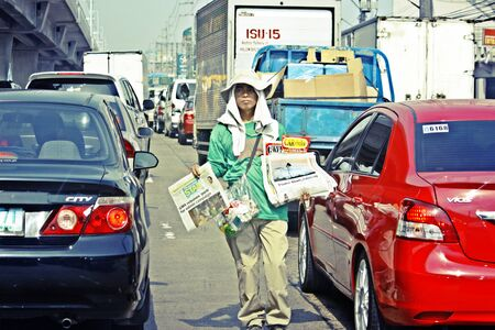 manila: MANILA-APR. 9- Filipino newspaper boy selling newspapers in the traffic and busy  streets of the city of Metro Manila taken on April 29, 2010 in Manila, Philippines. Editorial