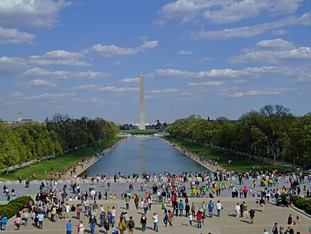 lincoln memorial: Photo of tourists looking at the Washington Monument, an obelisk built to commemorate George Washington, the first American president, standing almost due east of the Reflecting Pool and the Lincoln Memorial located in the National Mall in Washington, D.C