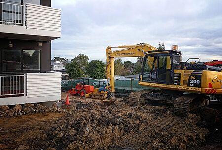 new construction: AUCKLAND-JUL. 14, 2015: A mechanical digger excavator in a construction site in Auckland, New Zealand. Editorial