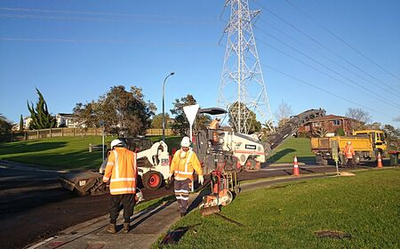 skid loader: AUCKLAND-JUL. 7, 2015: Construction workers repairing,sealing and paving the asphalt  road in Lynfield, Auckland, New Zealand. Editorial