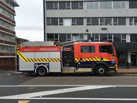 AUCKLAND, MAY 8: A Fire and Emergency New Zealand or New Zealand Fire Service fire truck or appliance parked on side of road viewed from side in Auckland, New Zealand taken on May 8, 2018.